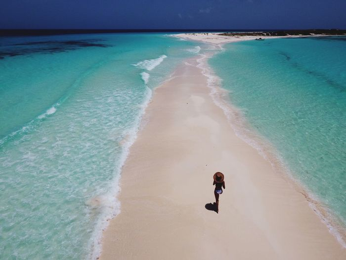 High Angle View Of Woman Walking On Shore Amidst Sea During Summer
