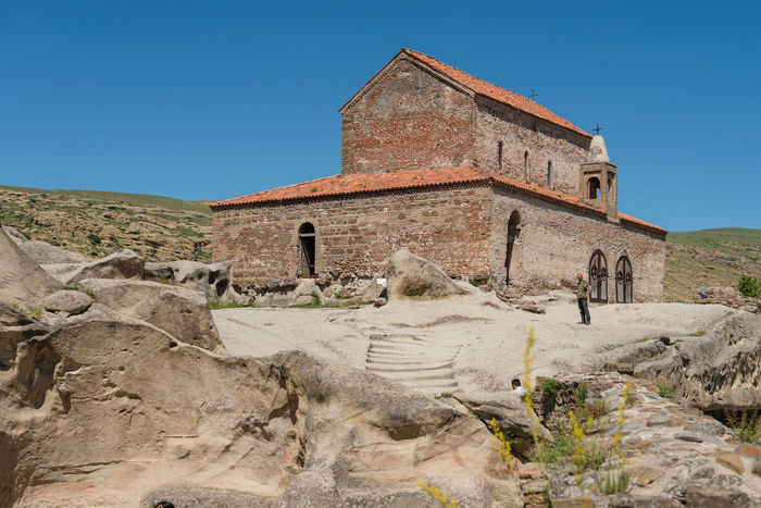 GEORGIA. UPLISTSIKHE CAVE TOWN - JUNE 13, 2017: Tourists walks through the cave city. The oldest stone church is built in the highest point of the city. Ancient Antique Archeology Church Georgia Lost Ruins Uplistsikhe Cave City Cave Town Civilization Rocks Stone Temple
