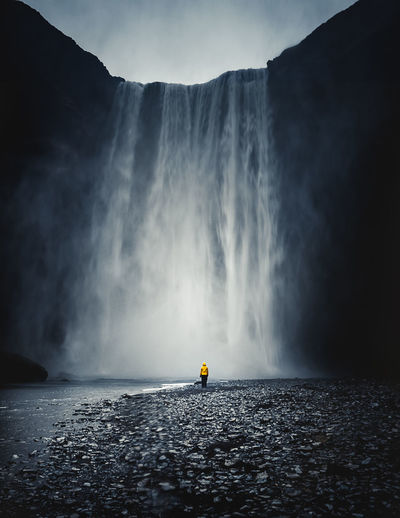 Tourist Looking At Majestic Waterfall