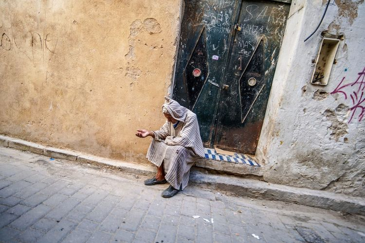 Hand to God. Fes Morocco Medina Medina De Fez Fes Morocco Ancient One Person Architecture Full Length Building Exterior Built Structure Real People Day Lifestyles Footpath Sitting Casual Clothing Building Leisure Activity Clothing Street Holding Outdoors Wall - Building Feature Adult Warm Clothing