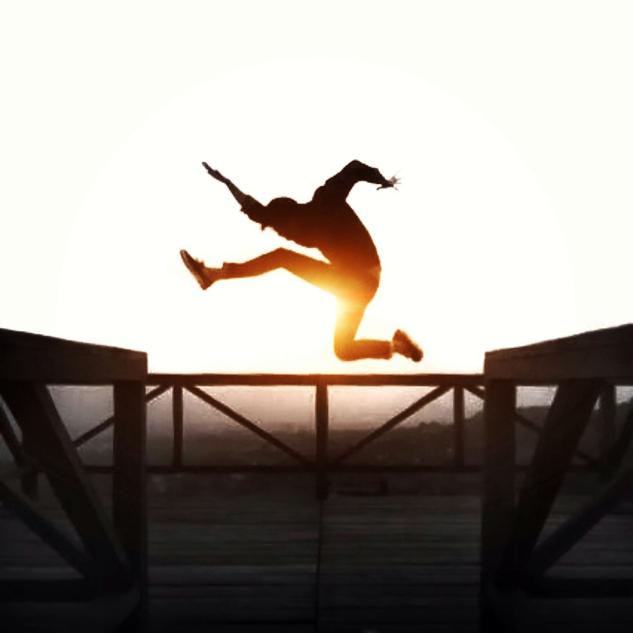 mid-air, jumping, full length, low angle view, lifestyles, leisure activity, silhouette, men, sunset, flying, clear sky, vitality, fun, sky, enjoyment, motion, freedom, arms outstretched