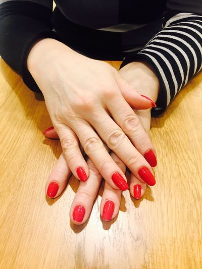 Cropped hands showing red nail polish on table
