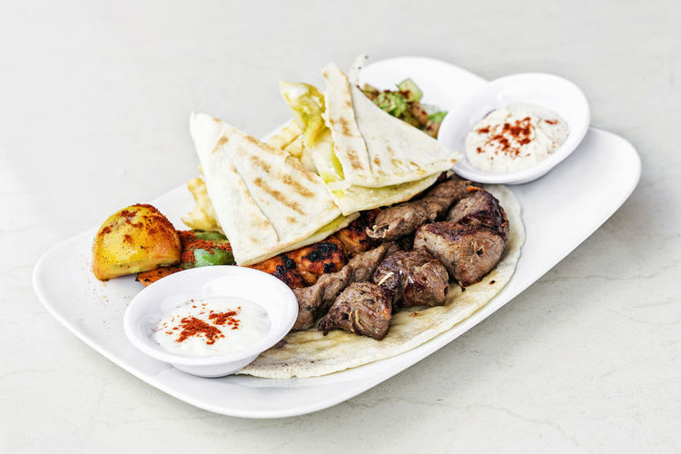 middle eastern grilled meat traditional meal Lebanese Food Meal Bbq Meat Beef DIP Food Garnished Gourmet Grill Grilled Meats Healthy Eating High Angle View Meat Middle Eastern Food Pita Bread Plate Set Meal Tortilla - Flatbread Traditional White Background