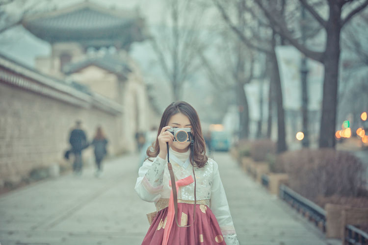 Lao girl is wearing Korean clothing, and taking photos My Best Travel Photo Seoul, Korea Adult Beautiful Woman City Clothing Focus On Foreground Hair Hairstyle Korean Culture Korean Girl Korean Style Lifestyles One Person Outdoors Photography Themes Real People Standing Street Streetphotography Tree Women Young Adult