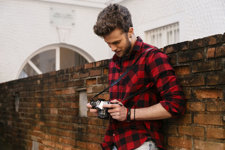 Adult Adults Only Brick Wall Camera - Photographic Equipment Casual Clothing Day Holding Leisure Activity One Man Only One Person Only Men Outdoors People Photographer Photographing Photography Themes Standing Technology Young Adult Young Men