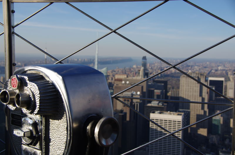 Close-up of coin-operated binoculars by fence against city against sky