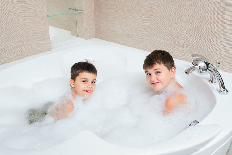 Portrait Of Smiling Boys Sitting In Bathtub