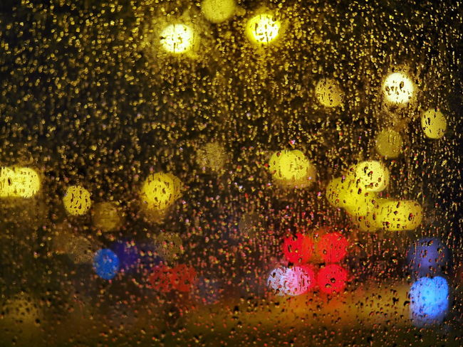 Rainy night from bus window focused rain drops blurry colorful street view
