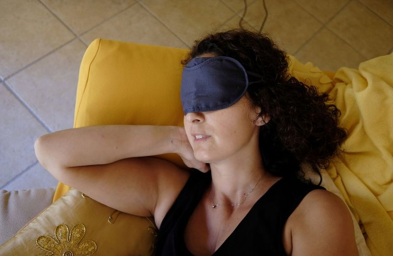 Woman wearing eye mask while sleeping on bed at home