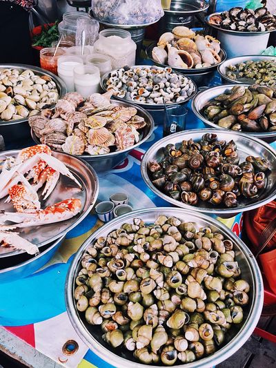 High angle view of various seafood in containers for sale at street market