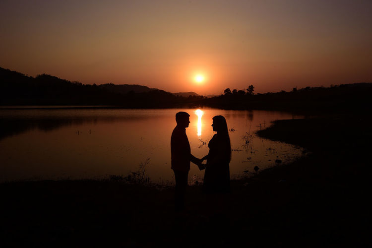 Silhouette boy and girl' standing on shore against sky during sunset