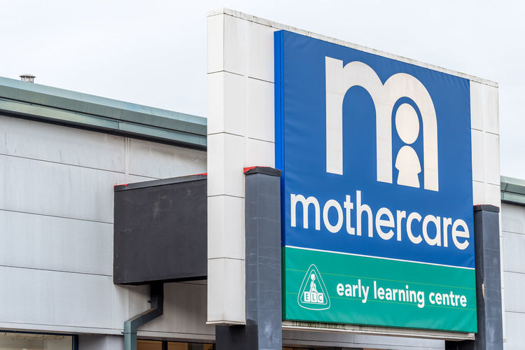 View of a Mothercare Logo in Nene Valley Retail Park Logo Architecture Blue Brand Building Exterior Communication Day For Mother Front View Mothercare No People Outdoors Road Sign Shop Text Transportation