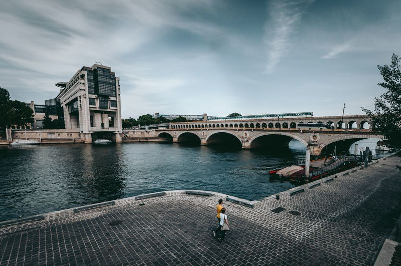 Bercy Nikonphotography Nikon Photography Metro Exploring Paris Bridge - Man Made Structure Architecture Connection Arch Built Structure Transportation Sky Real People Water Cloud - Sky Day River Outdoors City Building Exterior
