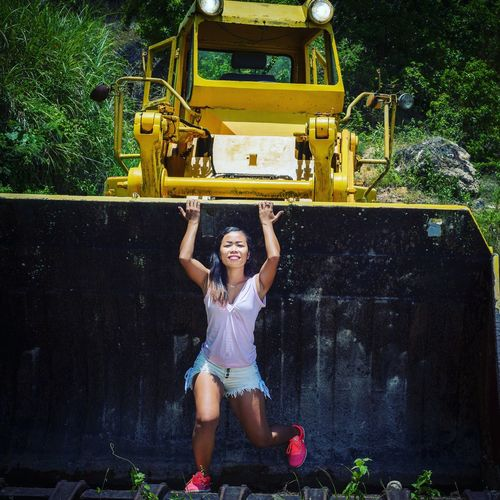 Full length of woman holding earth mover