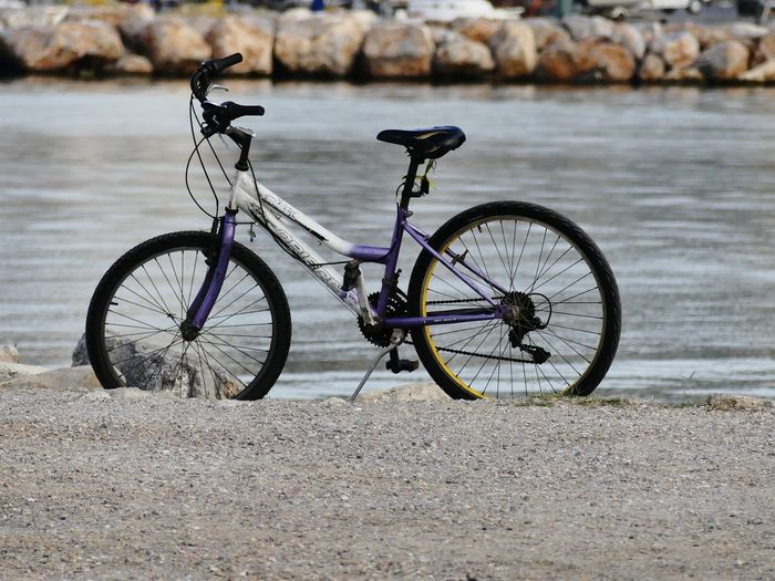 Side view of bicycle parked on riverbank