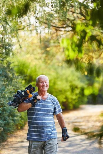 Portrait Of Smiling Senior Man Holding Roller Skates While Walking On Footpath