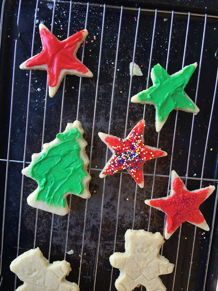 Holiday cookies on a rack, one broken Baking Cookies Baking Rack Christmas Cookies Close-up Cookie Sheet Decoration Festive Food Preparation Green Holiday Desserts Icing Cookies Multi Colored Natural Light Nobody Overhead Phone Camera Red Shapes Sprinkles Teddy Bear Shapes Vertical