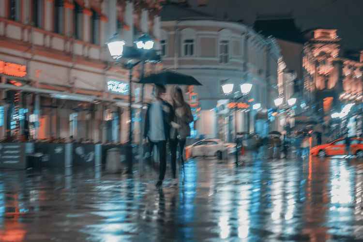 Young couple walking under umbrella, rainy late evening, happy together. Bright illumination, reflection in wet pavement. Concept of modern city, love, lifestyle. Abstract blurred background Illuminated City Night Motion City Rainy Rain Blurred Motion Blur Abstract Evening Street Bright People Reflection Lamps Pavement Umbrella Love Two Couple Girl Walking Lifestyles Outdoors