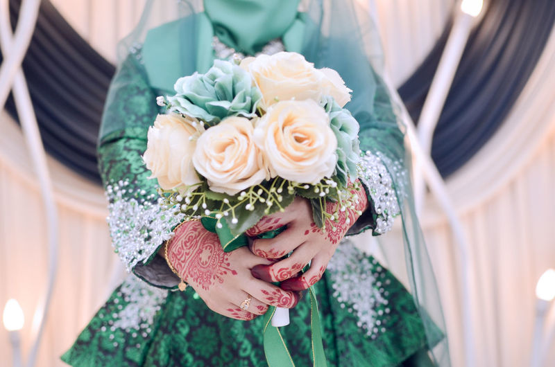 Midsection Of Bride Holding Rose Bouquet During Wedding