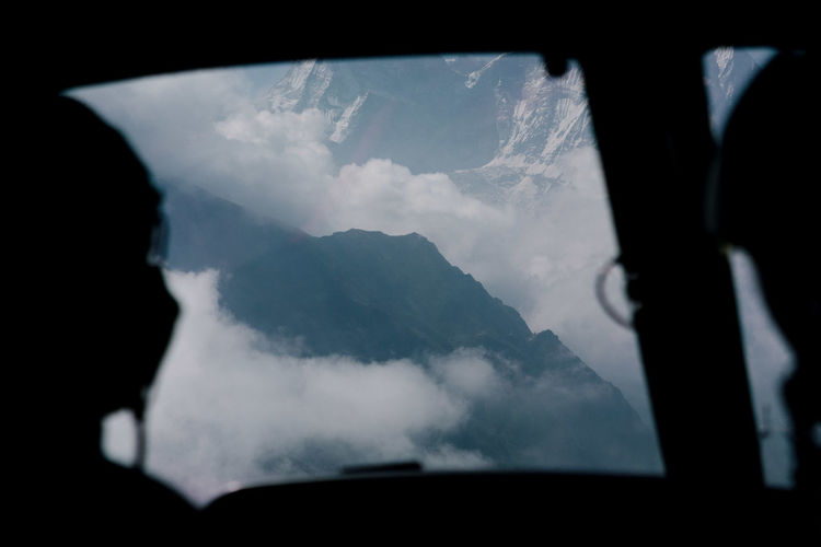 Silhouette pilots flying plane over mountain