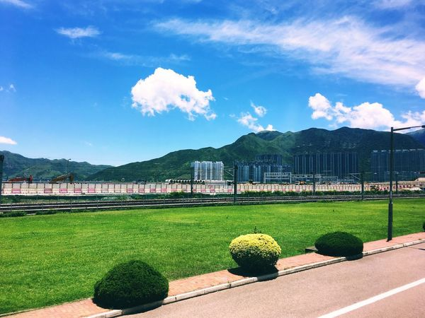 Sky Grass Day Cloud - Sky Built Structure Architecture Growth Green Color Mountain Tree Blue Nature Outdoors No People Plant Beauty In Nature Travel Destinations Building Exterior Soccer Field Tim Wong