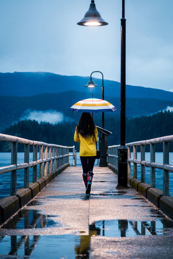 Rear view of woman with umbrella walking on pier over lake against mountains