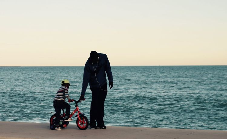 Father and son Family Adult Beach Black People Bonding Child On Bicycle Clear Sky Father Full Length Horizon Over Water Leisure Activity Lifestyles Men Nature Outdoors Parent And Child People Real People Red Bicycle Scenics Sea Sunset Togetherness Two People Water