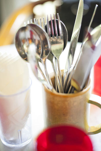 Close-up of fork and spoons in mug on table