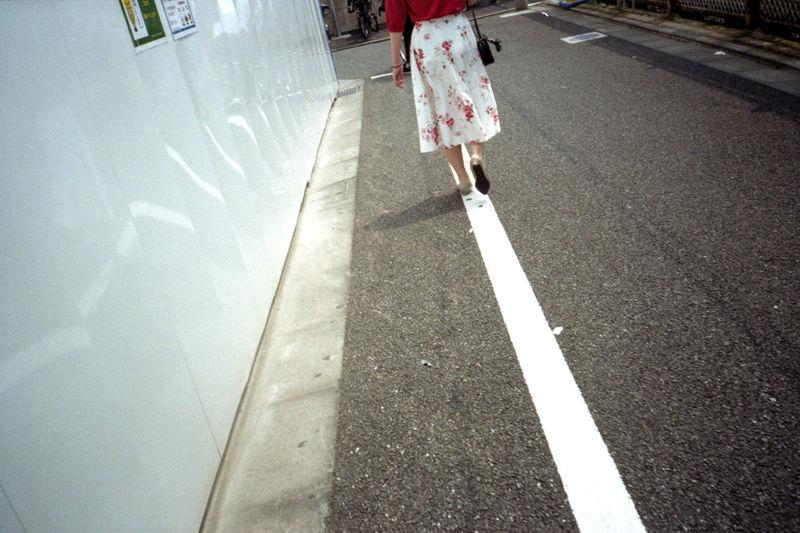 Low section of women walking on road
