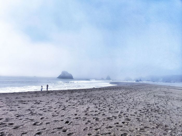 Foggy Misty day at the ocean. Two young people at the beach. Surreal. Background. Two Young People Beach Walking Wandering Meandering Foggy Misty Fog Surreal Background Footprints Zen Peaceful Restful Stunning Water Sea Beach Sand Sky Horizon Over Water Tide Coastline Calm Countryside Ocean Surf Wave Low Tide