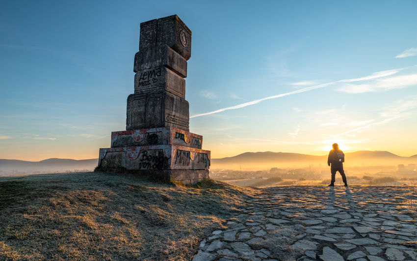 Man leaning on stone wall against sky during sunset