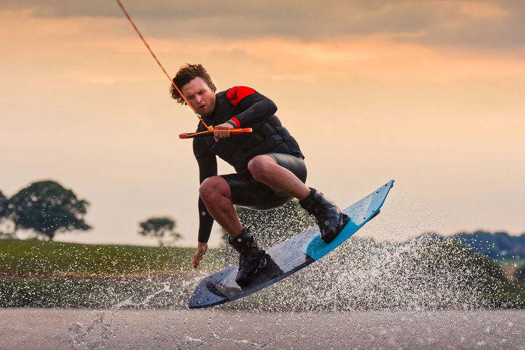 Full length of man wakeboarding against sky