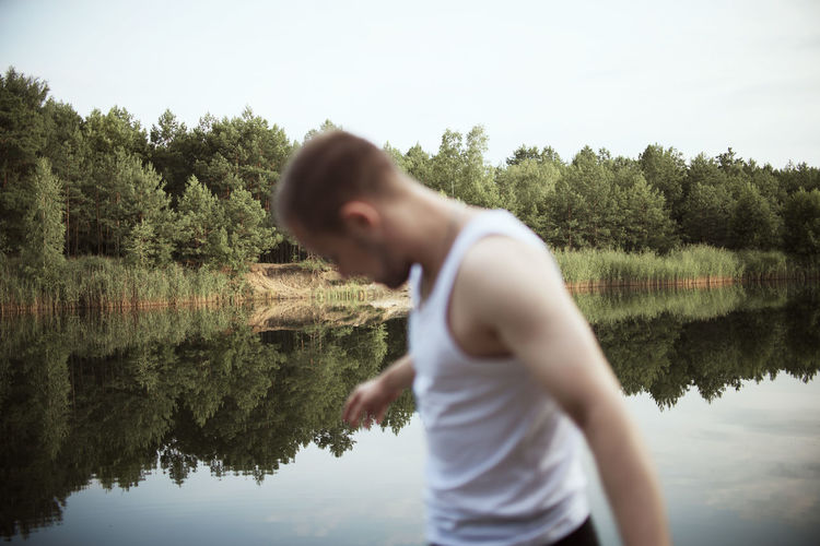 Side view of man standing by lake against sky