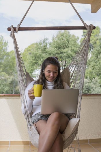 Midsection of woman using laptop while sitting outdoors