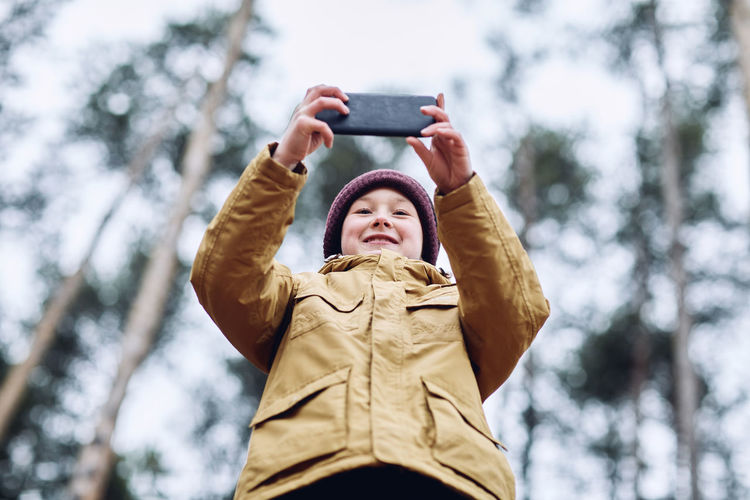 Low angle view of boy using mobile phone in winter