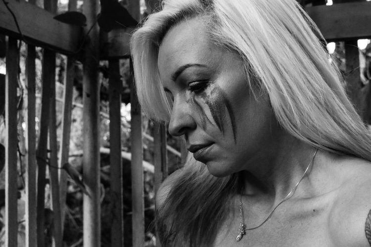 Close-up of thoughtful woman with face paint looking down by fence