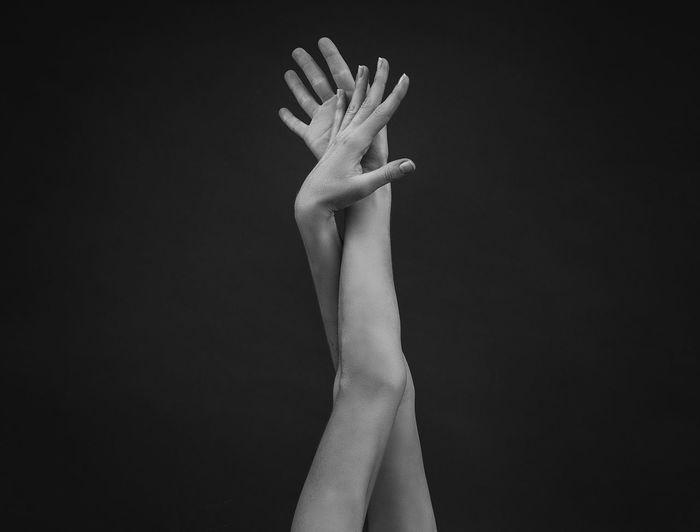 Close-up of woman hand against black background