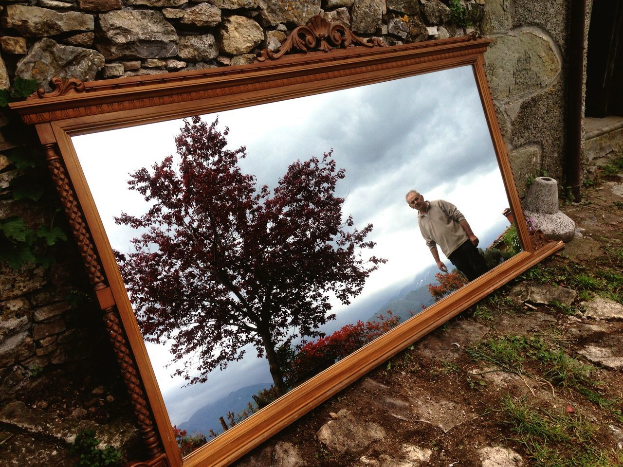 Reflection of mature man and tree on mirror leaning on wall at field