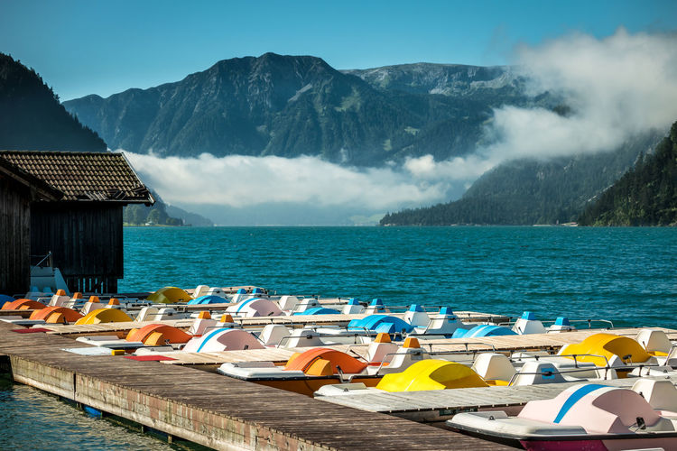 Boats Moored In River Against Mountains On Sunny Day