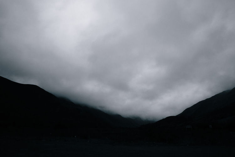Mountain Sky Cloud - Sky Beauty In Nature Scenics - Nature Tranquility Tranquil Scene Silhouette Nature No People Storm Non-urban Scene Environment Landscape Mountain Range Outdoors Idyllic Storm Cloud Overcast Dark Ominous Mountain Peak