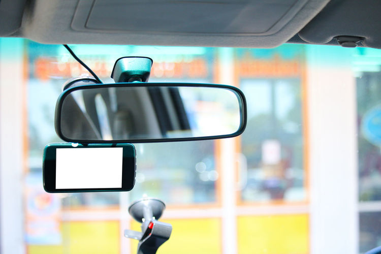Close-up of smart phone hanging on rear-view mirror in car