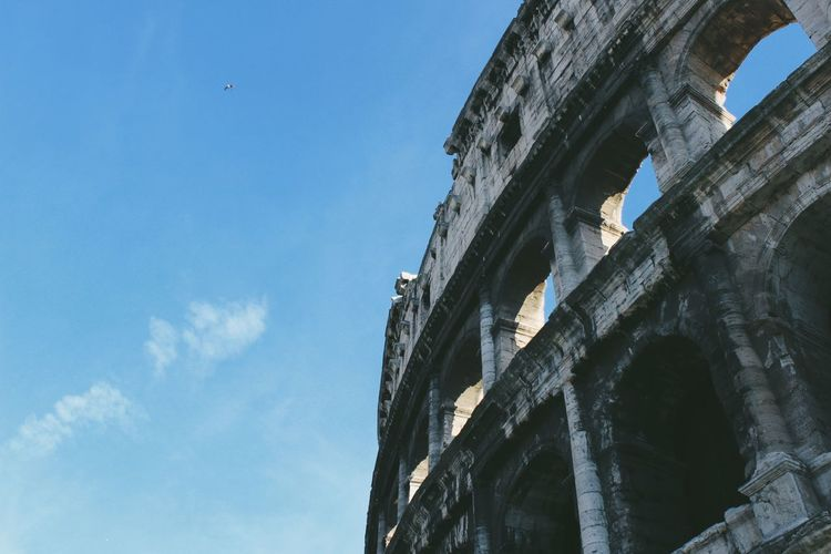Low angle view of colosseum against sky in city
