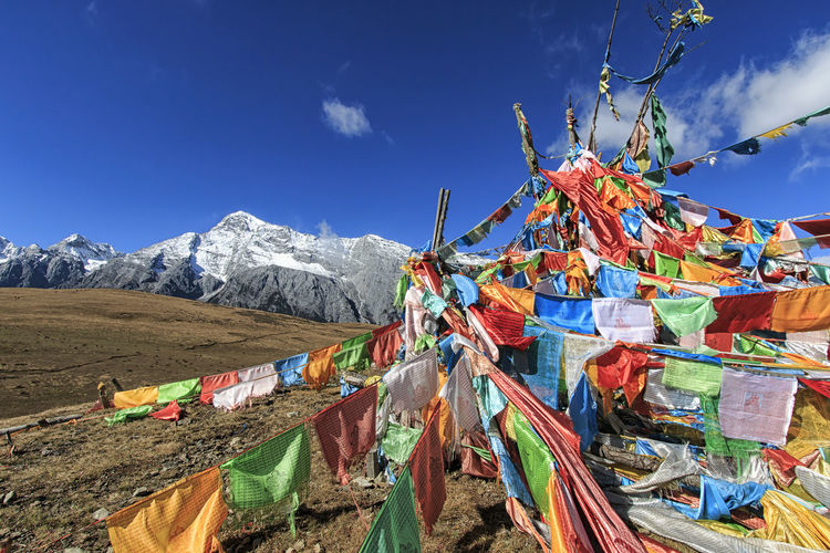 Multi Colored Praying Flags And Jade Dragon Snow Mountain Against Sky