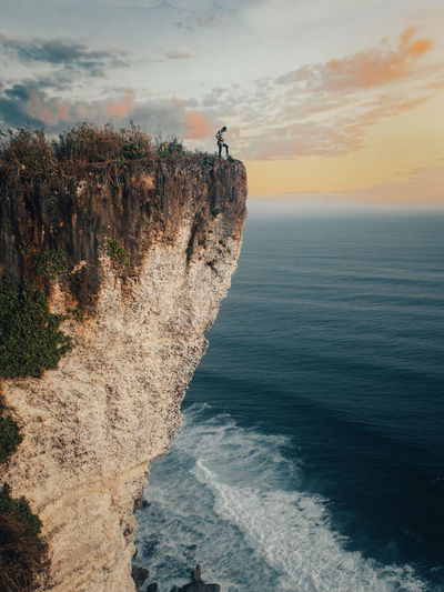 Full length of man standing on cliff against sea and sky