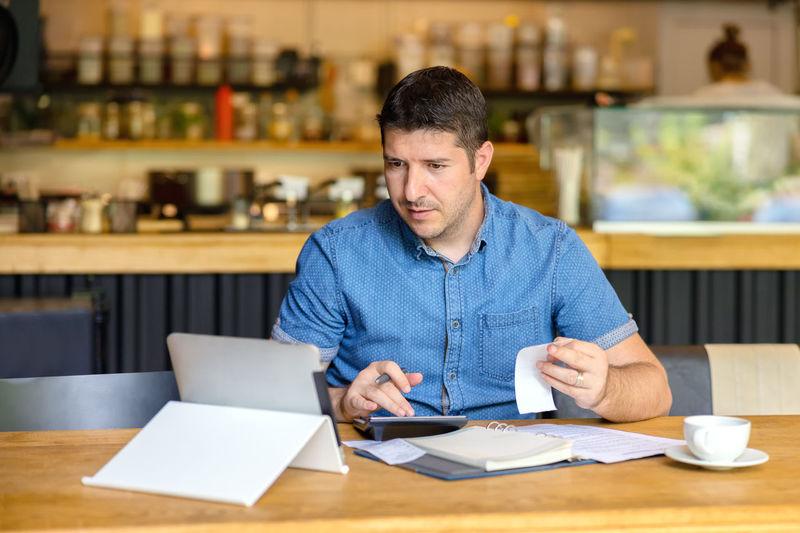 Man using calculator while looking at digital tablet