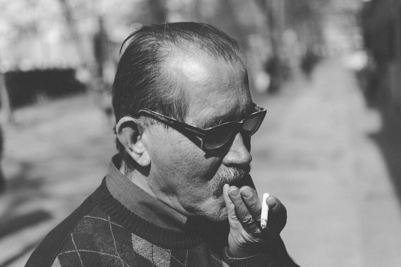 Close-up of senior man smoking cigarette outdoors