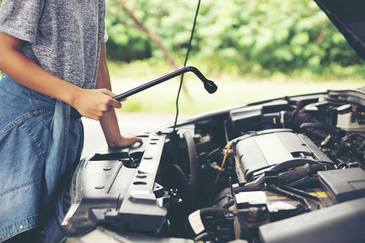 Midsection Of Mechanic Repairing Car Outdoors