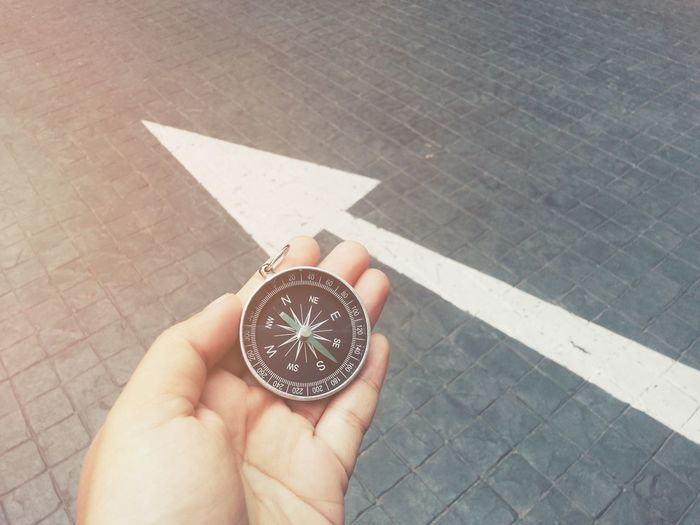Hand holding compass with white arrow background Compass Navigation Business Guidance Navigator  Direction Travel Trip Map Way Journey Advanture Voyage Lost Lifestyle Cartography Success Arrow Destination North East West South Mission