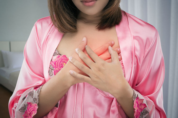 Midsection of woman suffering from chest pain at home