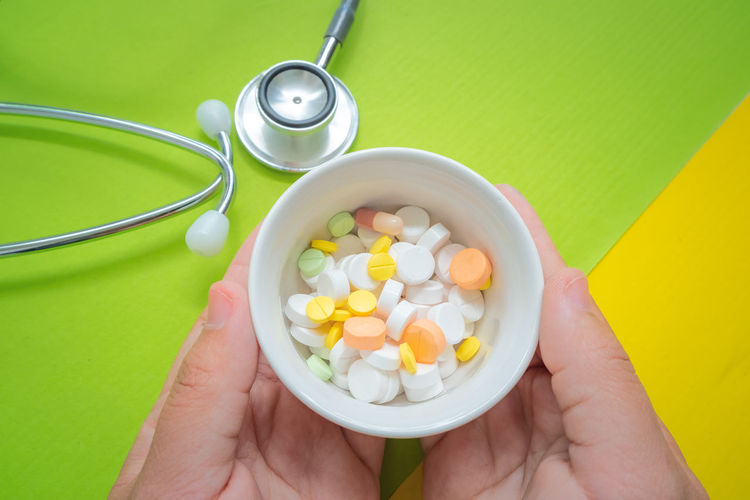 Close-up of person hands holding medicine in container by stethoscope over colored background